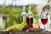 image of salami  - Two bottles of wine and glasses some grapes salami bread and cheese outside - JPG