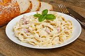 stock photo of carbonara  - Plate of tagliatelli carbonara italian food in a rustic restaurant setting - JPG