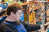 stock photo of dungarees  - man in dungarees in his workroom repairs a bike - JPG