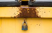 picture of dumpster  - a rusty yellow dumpster locked with a padlock - JPG