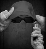 stock photo of incognito  - Incognito personification with cotton gloves glasses baseball cap and mobile phone