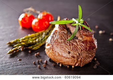 Piece of red meat steak with vegetable and herbs, served on black stone surface.