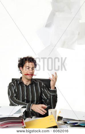 Hombre sentado en el escritorio vomitando papeleo