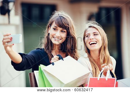 Two young women shopping at the mall taking a