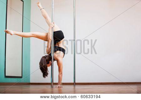 Strong brunette pole dancing