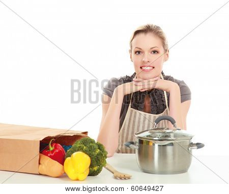 Woman in apron sitting on the desk with grocery bag , isolated on white background