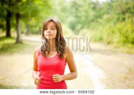Woman Jogging Through A Forest