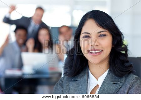 Businesswoman Smiling With Her Team Celebrating A Success In The Background