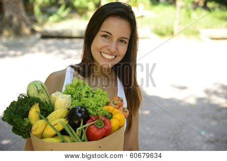 Happy woman carrying a bag full of organic food.