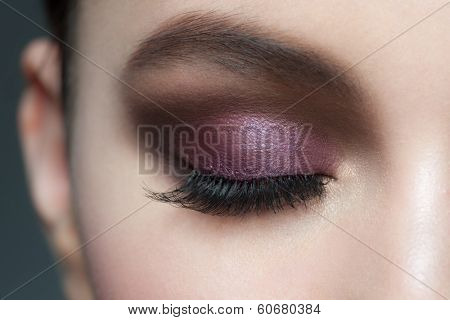 Closeup of beautiful woman eye with bright violet stylish makeup with long lashes