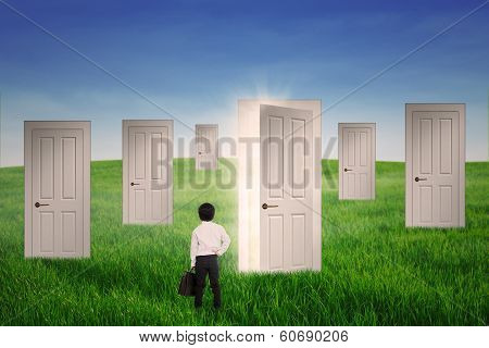 Business Boy Standing In Front Of Opportunity Doors