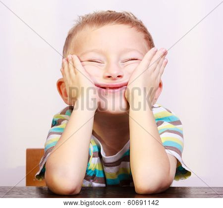Portrait Of Blond Boy Child Kid Making Funny Face At The Table
