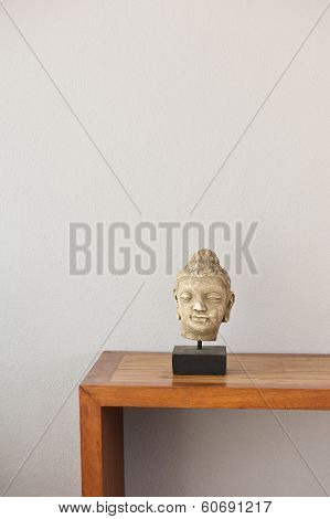 Buddha Head In Front Of A Grey Wall