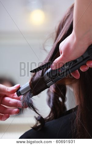 In Hairdressing Salon. Female Hair And Straightening Irons.