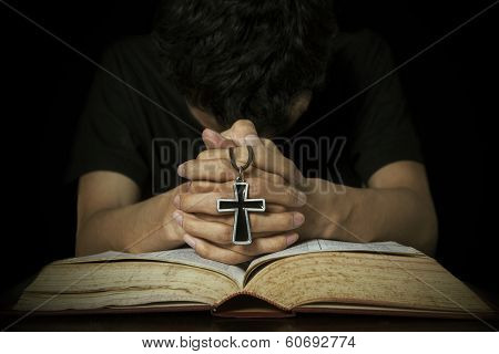 Man Praying With Bible And Cross