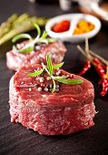 stock photo of ribeye steak  - Pieces of red raw meat steaks with rosemary served on black stone surface - JPG