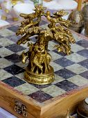 foto of krishna  - bronze chess piece showing the lord krishna sitting under a tree and playing the flute