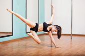 stock photo of pole dance  - Sexy young brunette practicing some moves in a pole dancing class at a gym - JPG