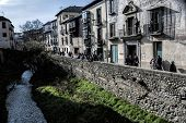 People Lhtteaned Out And The Balconies Of A Nineteenth Century Facade At The Feet Of The River Darro