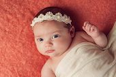 Portrait Of A Baby Girl Wearing A Lace And Pearl Headband