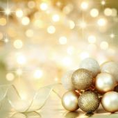 stock photo of sparkles  - Gold Christmas baubles and ribbon on background of defocused golden lights - JPG
