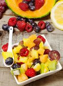 stock photo of greedy  - greedy fruit salad with and fruits background on wood table - JPG
