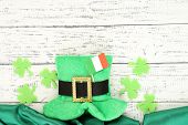 foto of irish flag  - Saint Patrick day hat with clover leaves and Irish flag on wooden background - JPG