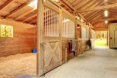 stock photo of stable horse  - Stable barn with beam ceiling and open door to a clean stall - JPG
