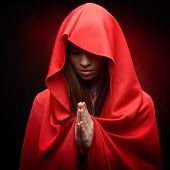 stock photo of cloak  - beautiful woman with red cloak in studio praying - JPG