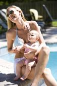 picture of swimming pool family  - Mother with six month old baby girl next to a swimming pool - JPG
