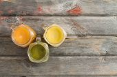 stock photo of jug  - Healthy refreshing tropical fruit juice served in three glass jugs on an old weathered wooden picnic table including mango orange and kiwifruit blends with copyspace - JPG