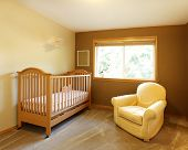 Baby Room With Crib And Yellow Chair.