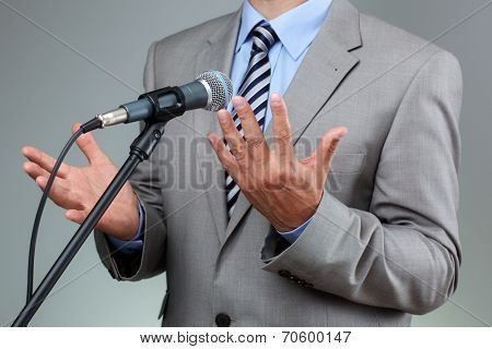 Businessman making speech with microphone and hand gesturing concept for explaining, protesting or belief
