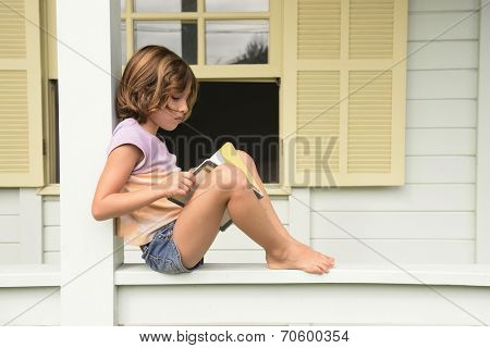 Child reading a book on balcony.