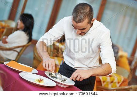 young male waiter prepairing fish food on tray serving at restaurant