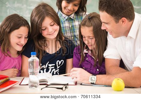 Cheerful kids learning in school with their teacher