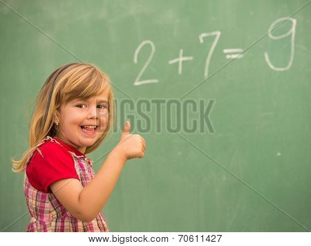 Adorable little school blonde girl in school classroom on board posing