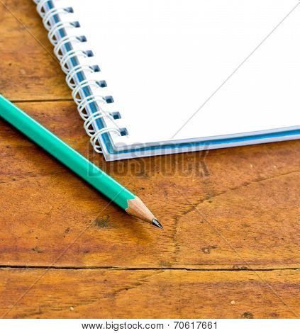 Pencils And Notebook On A Wooden Background