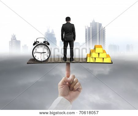 Businessman Standing Between Clock And Gold Balancing On Seesaw
