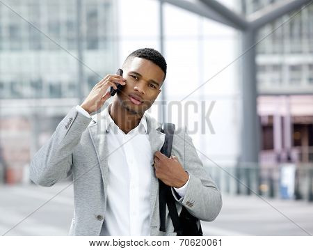 Cool Young Man With Bag Talking On Mobile Phone