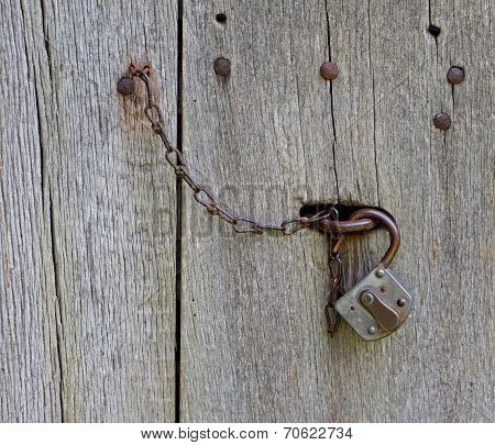 Lock And Chain On Old Wooden Door