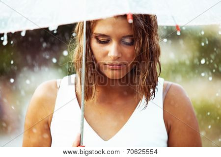 Portrait of sad young girl walking with umbrella under rain