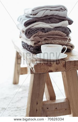 Still life details, stack of woolen sweaters on rustic bench on white carpet