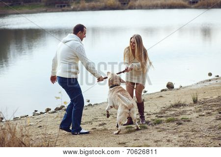 Young happy couple walking with dog near the lake in autumn