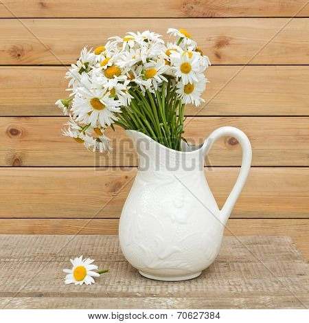 Bouquet Of Fresh  Daisies In Hite Jug On Wooden Background