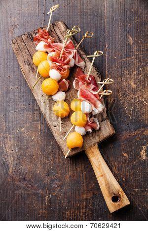 Mozzarella, Prosciutto, Melon Canapes On Dark Wooden Background