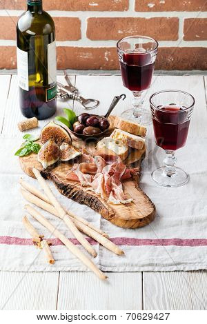 Prosciutto Ham, Olives And Red Wine On Olive Wood Cutting Board