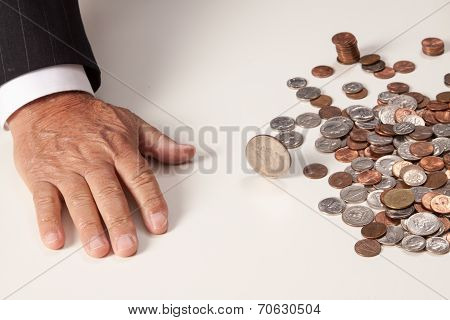 Man's hand flat after tossing coin that is spinning