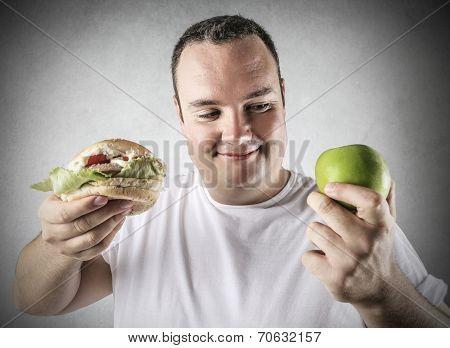 chubby man deciding whether to eat an apple or a hamburger