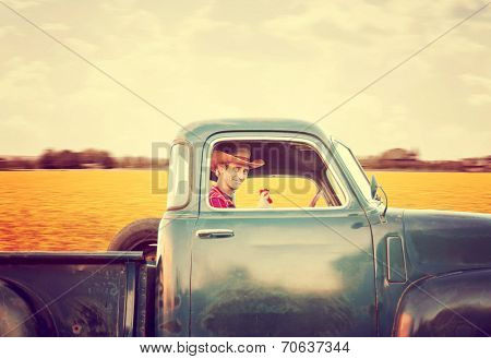 a handsome man with a cowboy hat on driving a truck past a field full of yellow flowers toned with a retro vintage instagram filter effect